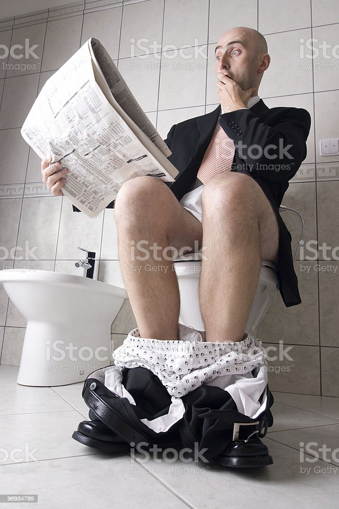 Reading newspaper on toilet royalty-free stock photo