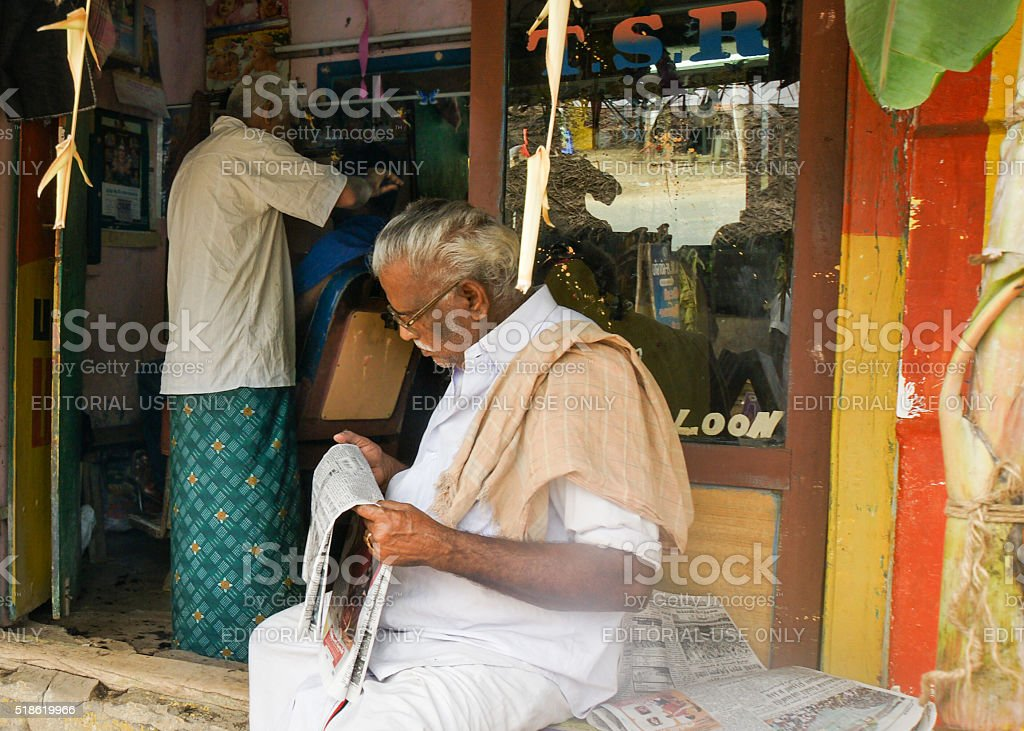 Reading newspaper while waiting at barber. stock photo