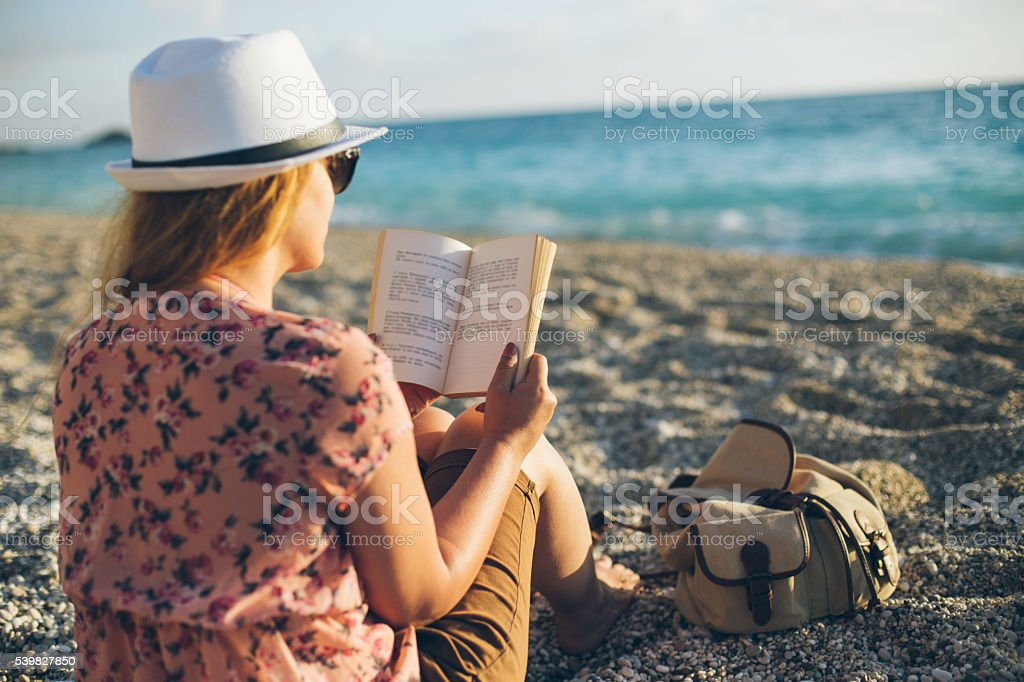 Reading on the beach stock photo