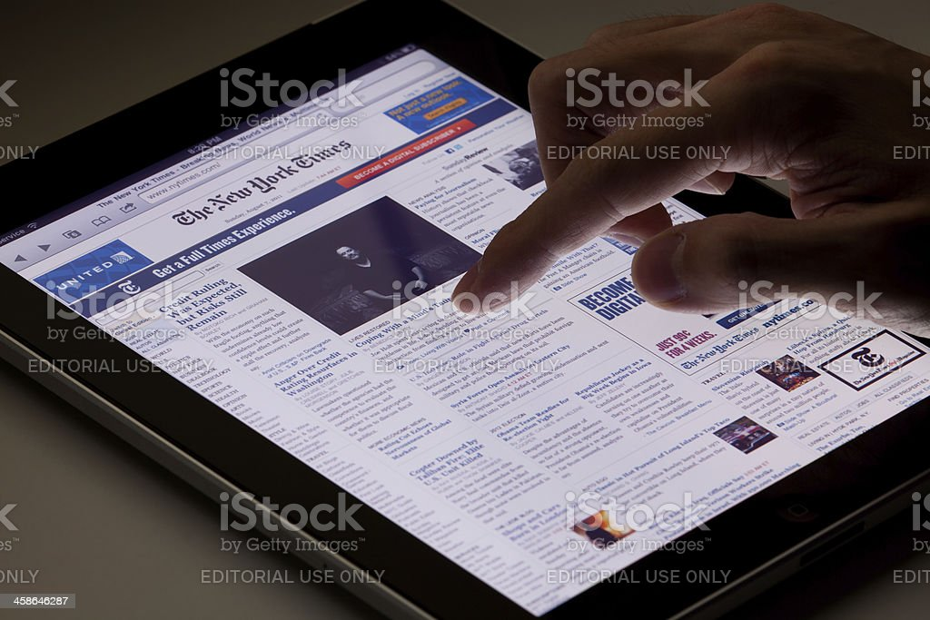 Reading online newspaper on ipad royalty-free stock photo