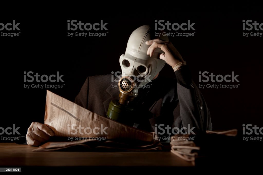 Reading the news with a gas mask stock photo