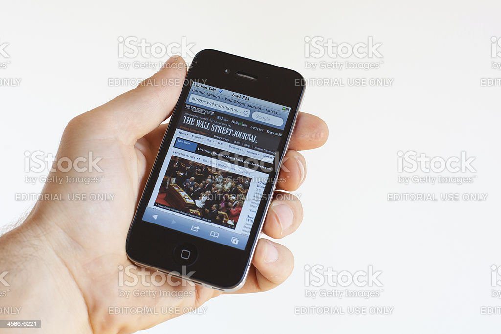 Reading the Wall Street Journal on Iphone 4 stock photo