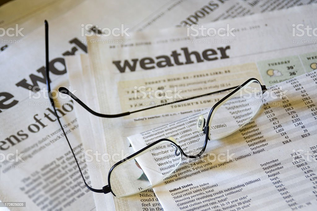 Reading Weather in Newspaper Media with Retirement Reading Glasses stock photo