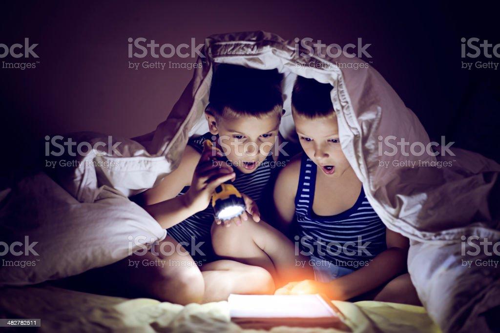 Reading with a flashlight stock photo