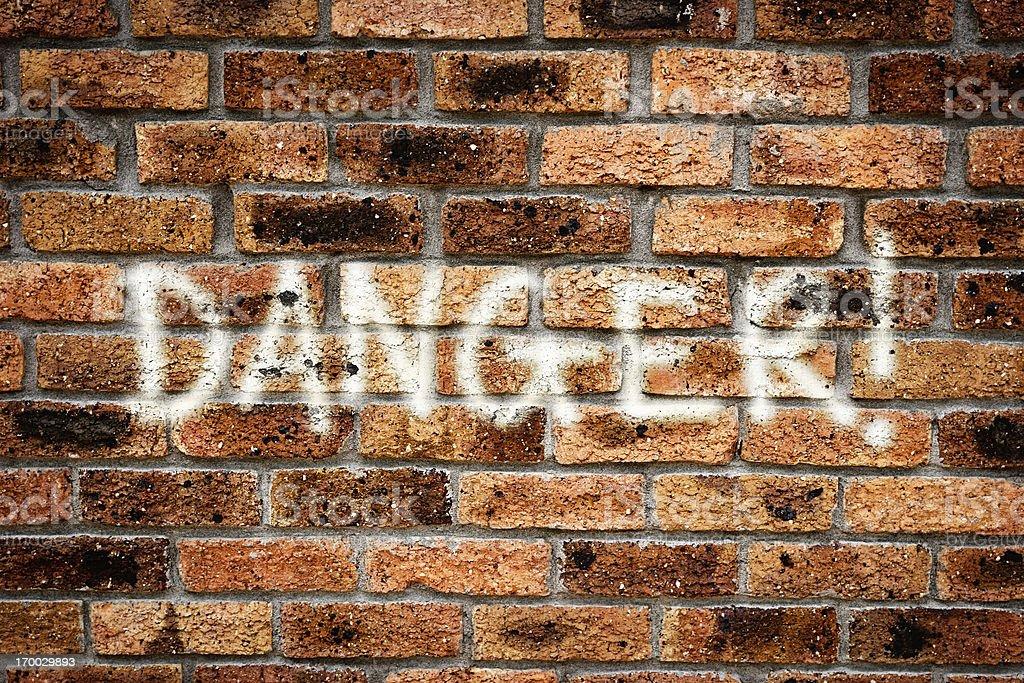 DANGER! reads warning graffiti on grungy brick urban wall royalty-free stock photo