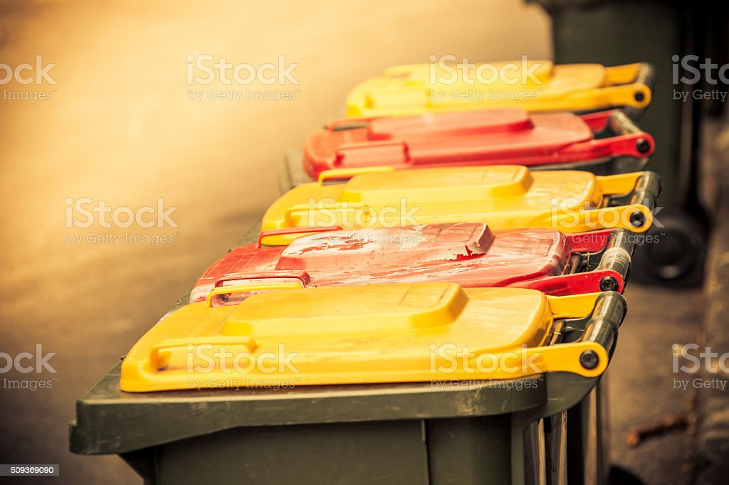 Ready for the garbos: yellow and red-topped garbage bins stock photo