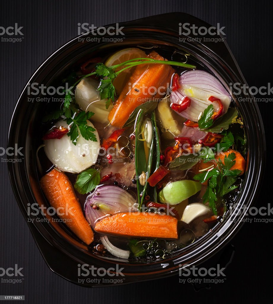 Ready to cook vegetable soup in pot on a dark surface stock photo