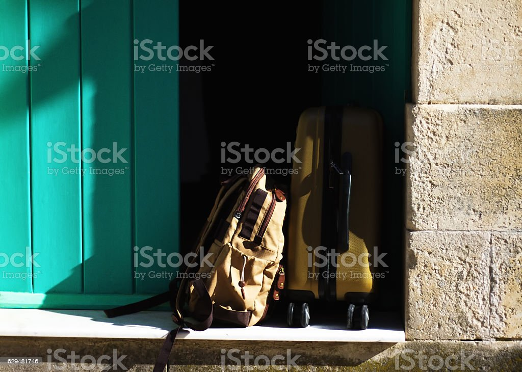 Ready to Escape: Suitcase and Backpack in Open Door stock photo