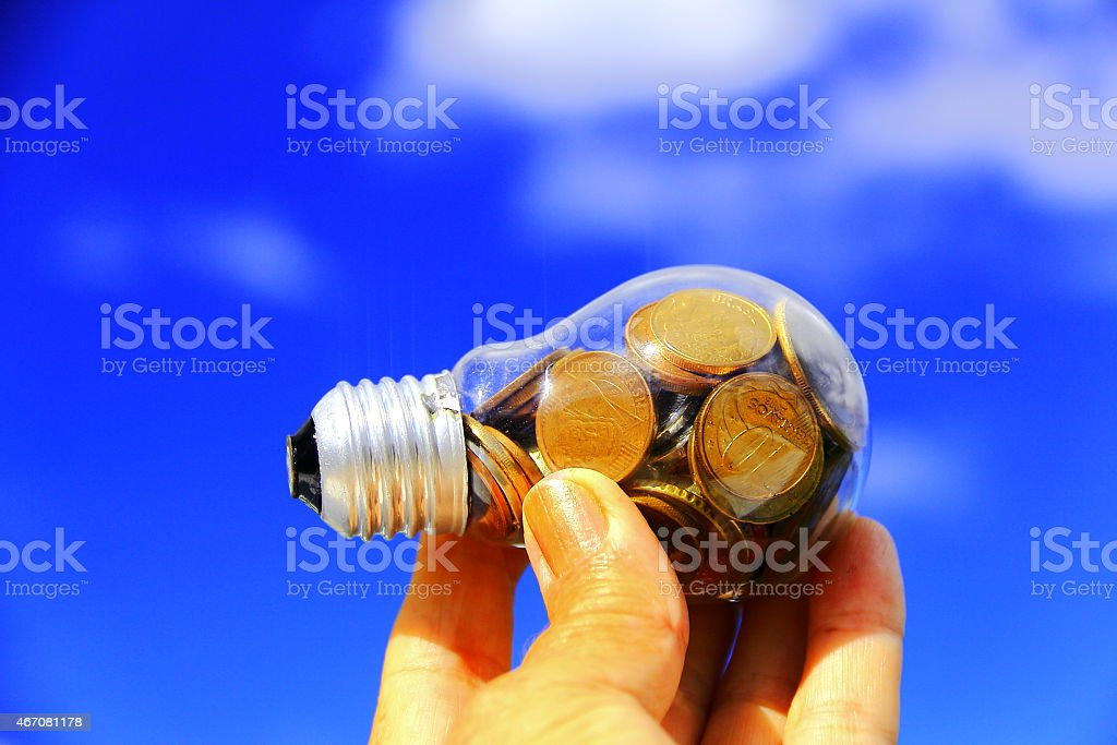 Real coins in light bulb - savings symbol. stock photo