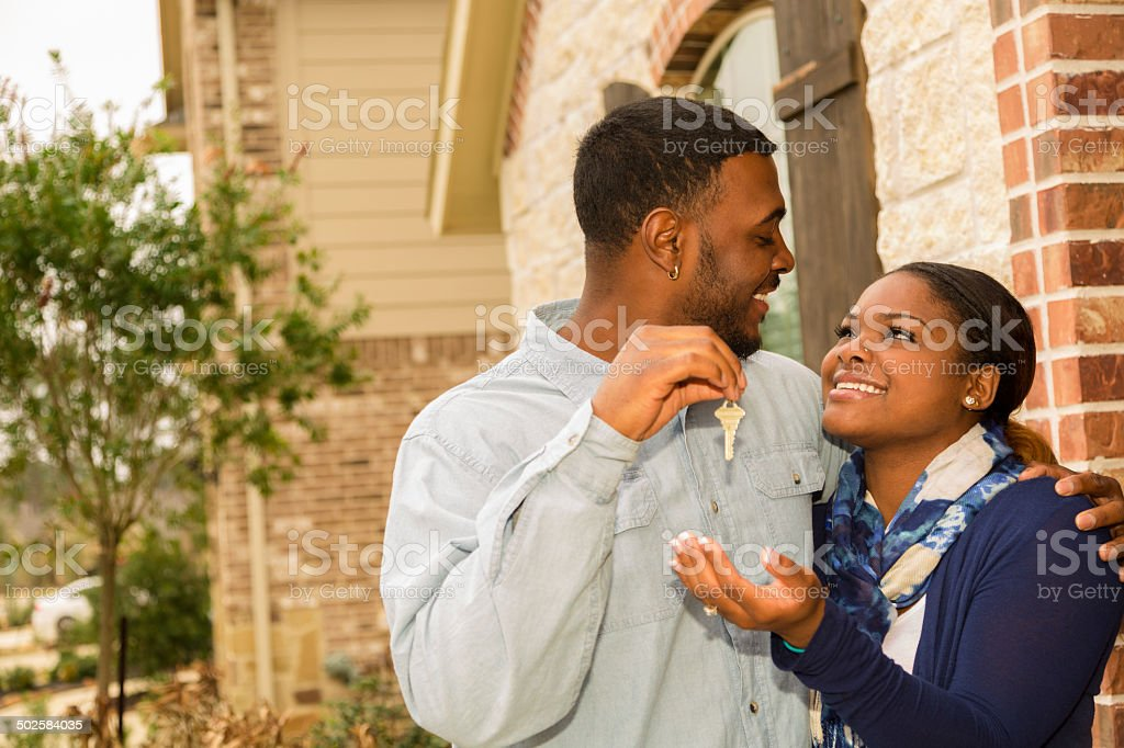 Real Estate: African descent couple buys home.  House key. stock photo