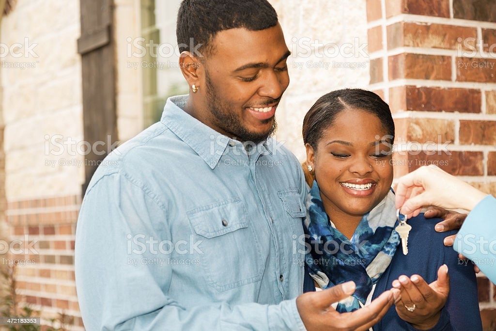 Real Estate: African descent couple buys home. House key, realtor. royalty-free stock photo