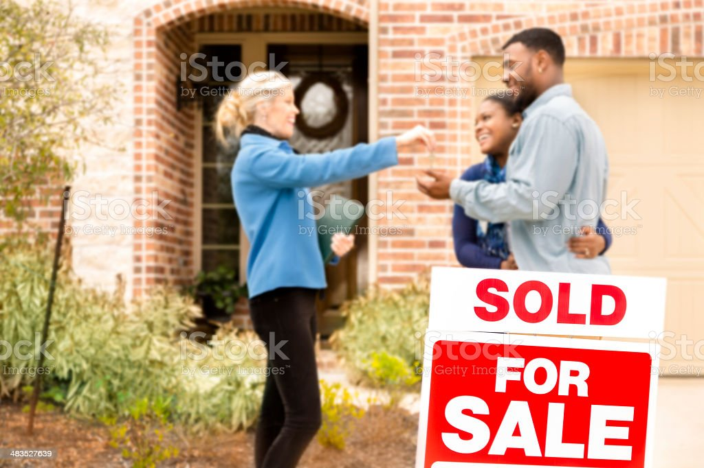 Real Estate: African descent couple buys home. Realtor gives key. stock photo