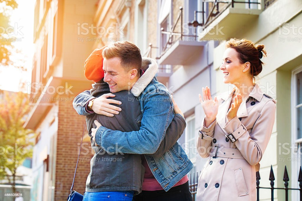 Real estate agent elated as couple hug over home purchase stock photo