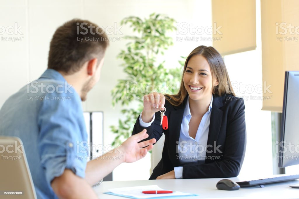 Real estate agent giving house keys to a customer stock photo