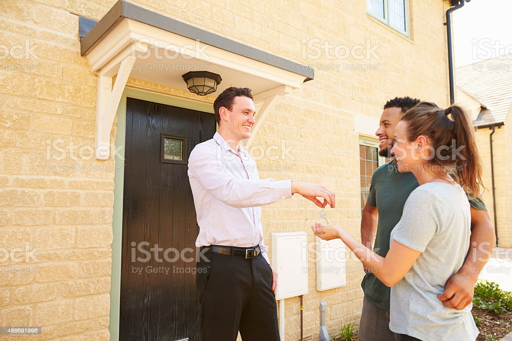 Real estate agent giving house keys to new property owners stock photo