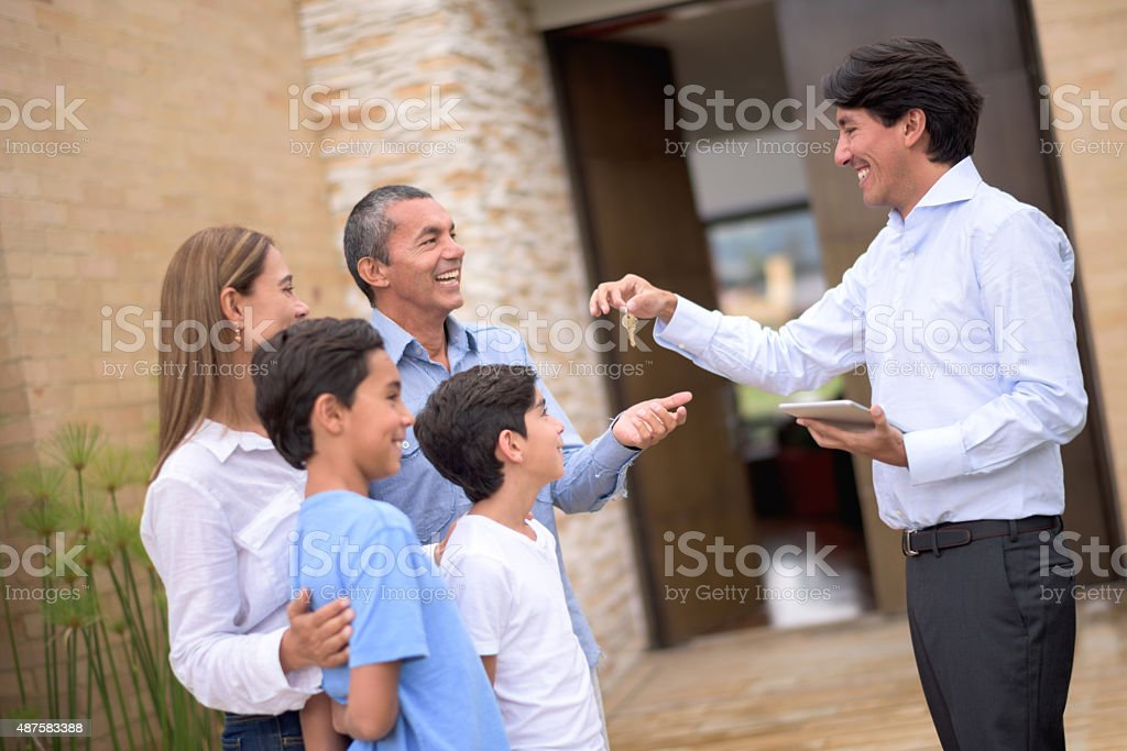 Real estate agent giving keys to a family stock photo
