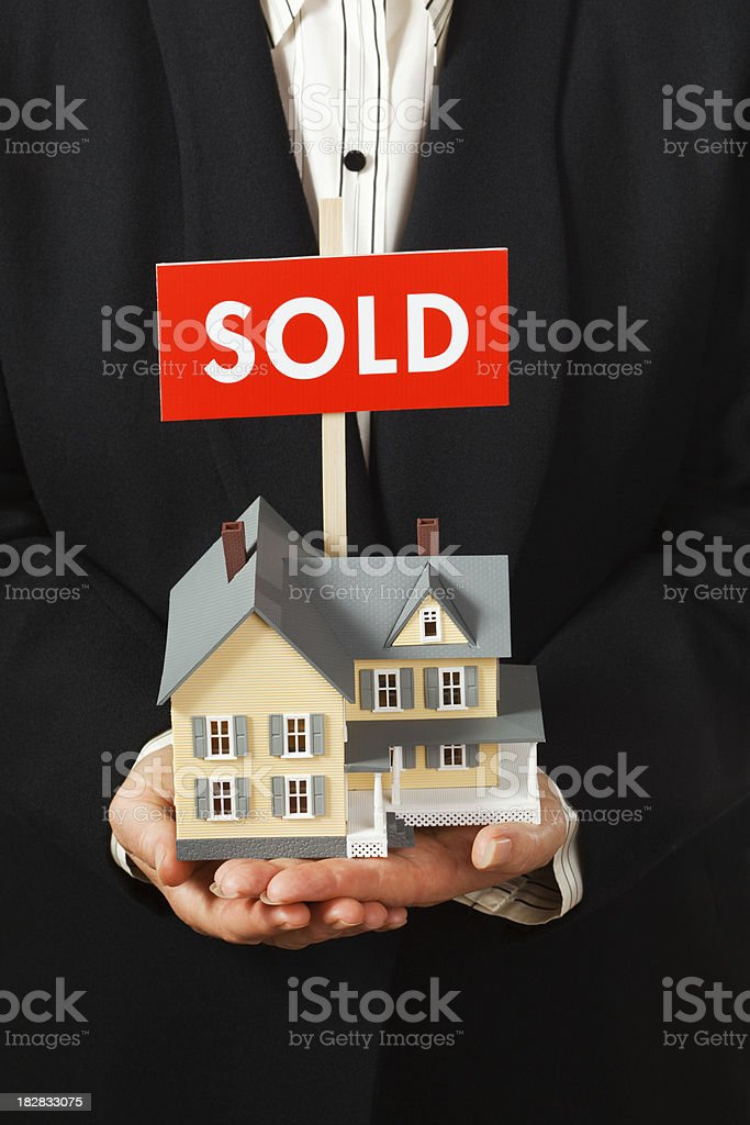 Real Estate Agent Holding a House with SOLD Sign Vt royalty-free stock photo