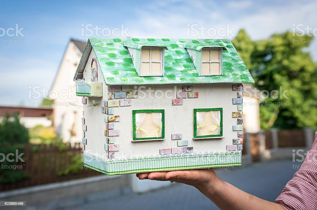 Real estate agent holding model house from paper stock photo