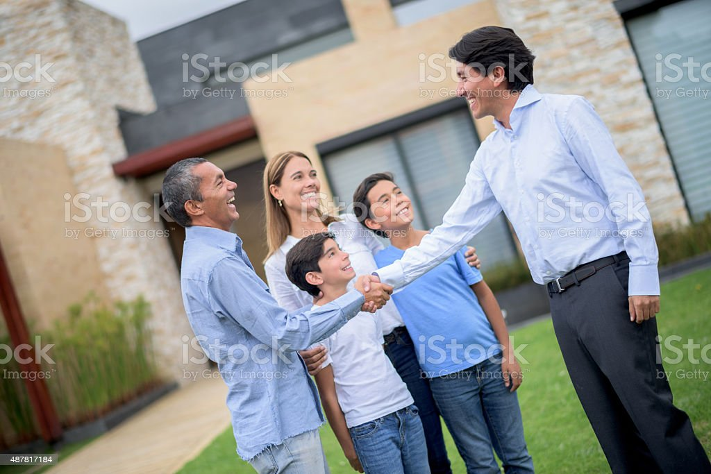 Real estate agent selling house to a family stock photo