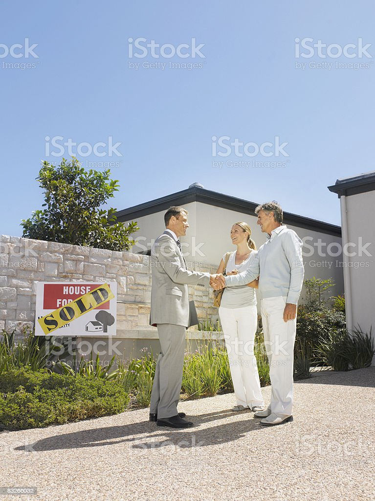 Real estate agent shaking hands with couple at new home royalty-free stock photo