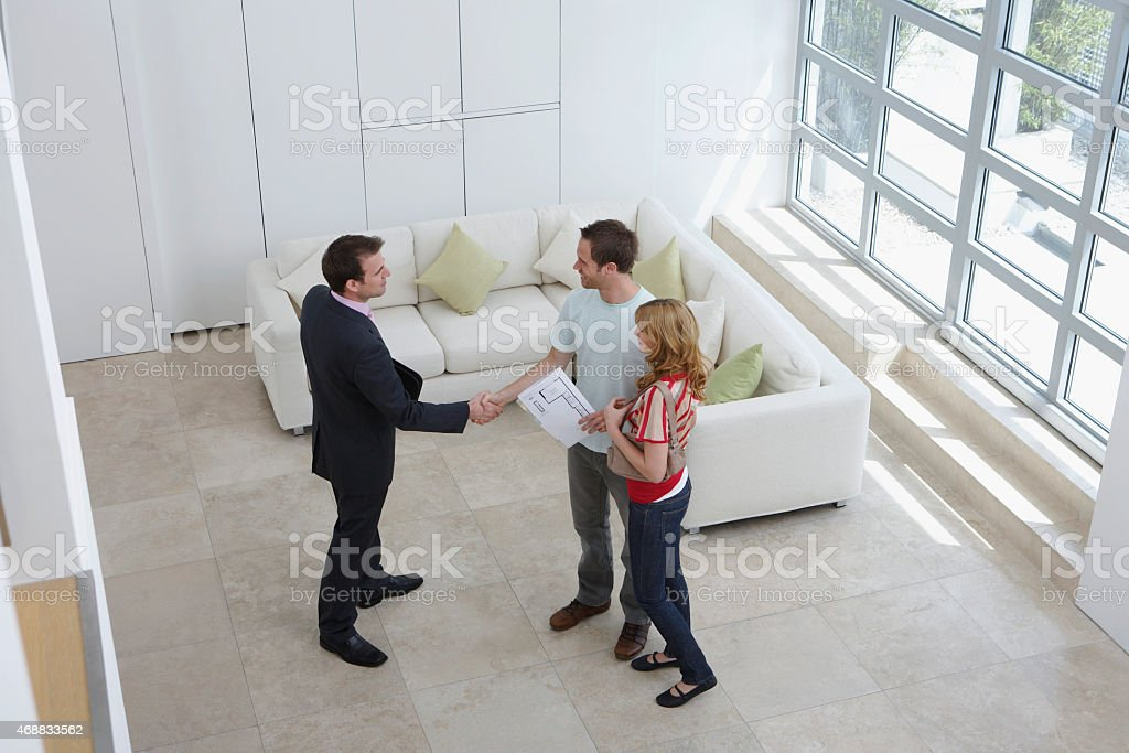 Real Estate Agent Shaking Hands With Man By Woman stock photo