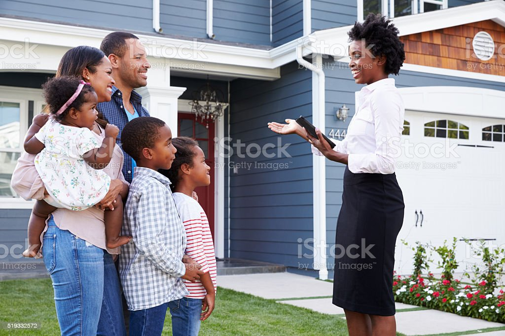 Real estate agent showing a family a house, closer in stock photo