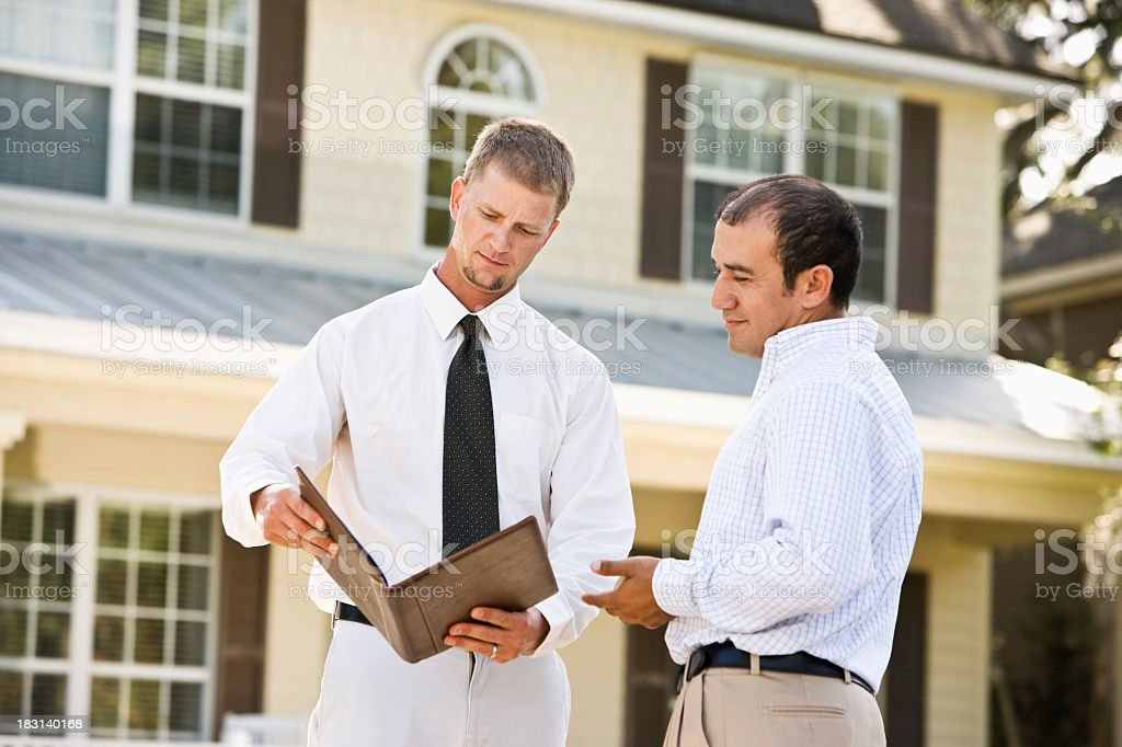 Real estate agent showing brochure in front of house royalty-free stock photo