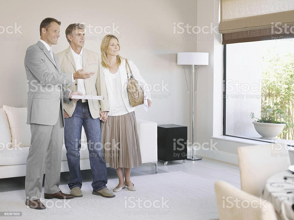 Real estate agent showing couple new home royalty-free stock photo