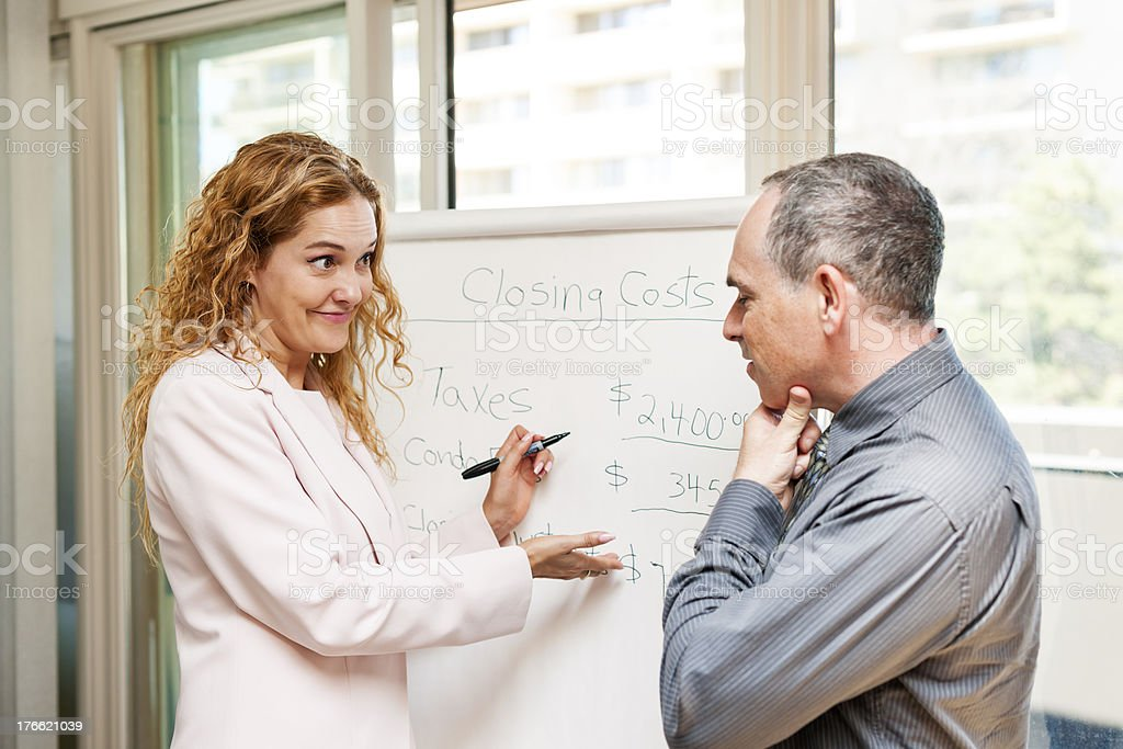 Real estate agent showing figures on a white board stock photo