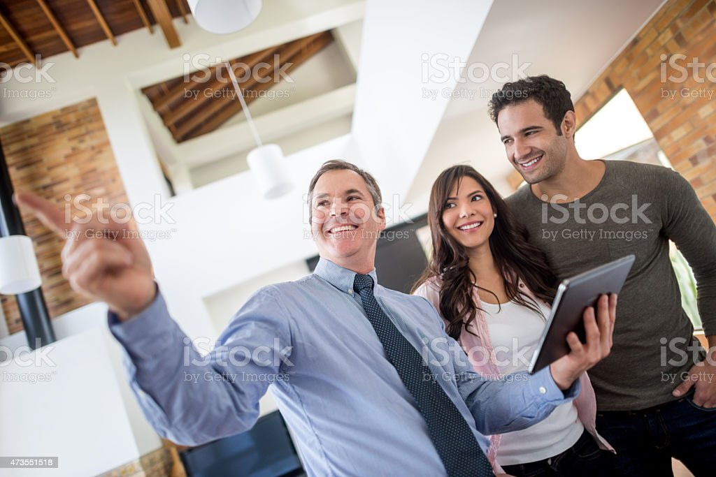 Real estate agent showing house to a couple stock photo