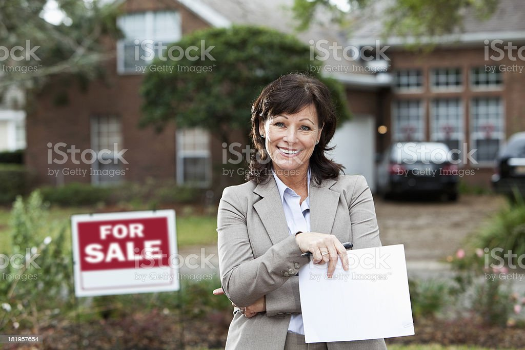 Real estate agent standing outside house stock photo