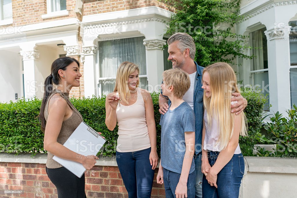 Real estate agent talking to a family stock photo