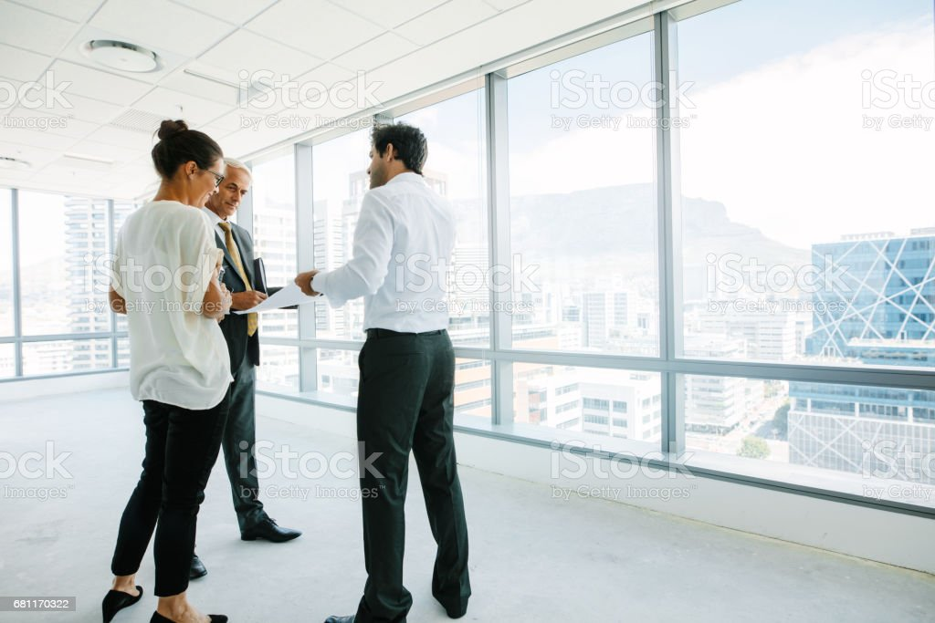 Real estate agent talking with potential clients at new office space stock photo