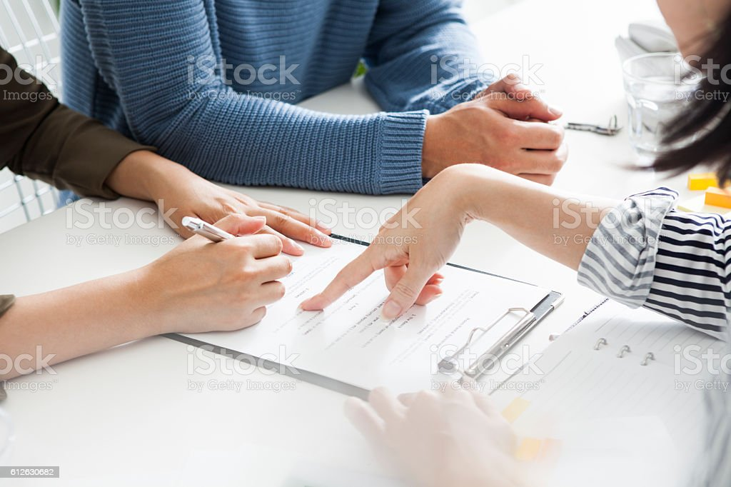 Real estate agent will show the contract to the couple. stock photo