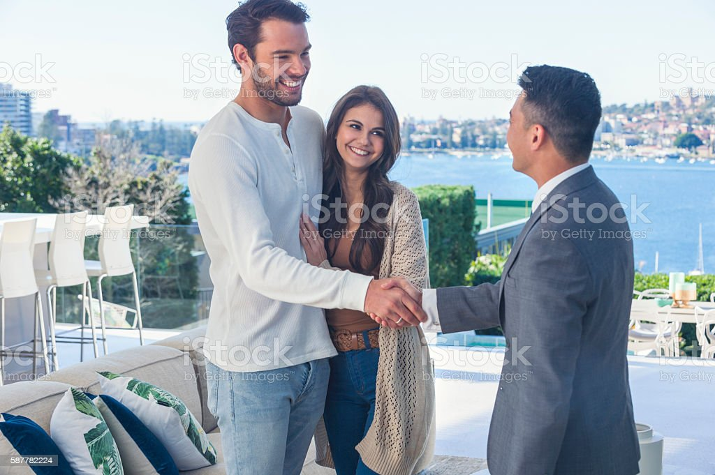 Real estate agent with couple in luxury home. stock photo
