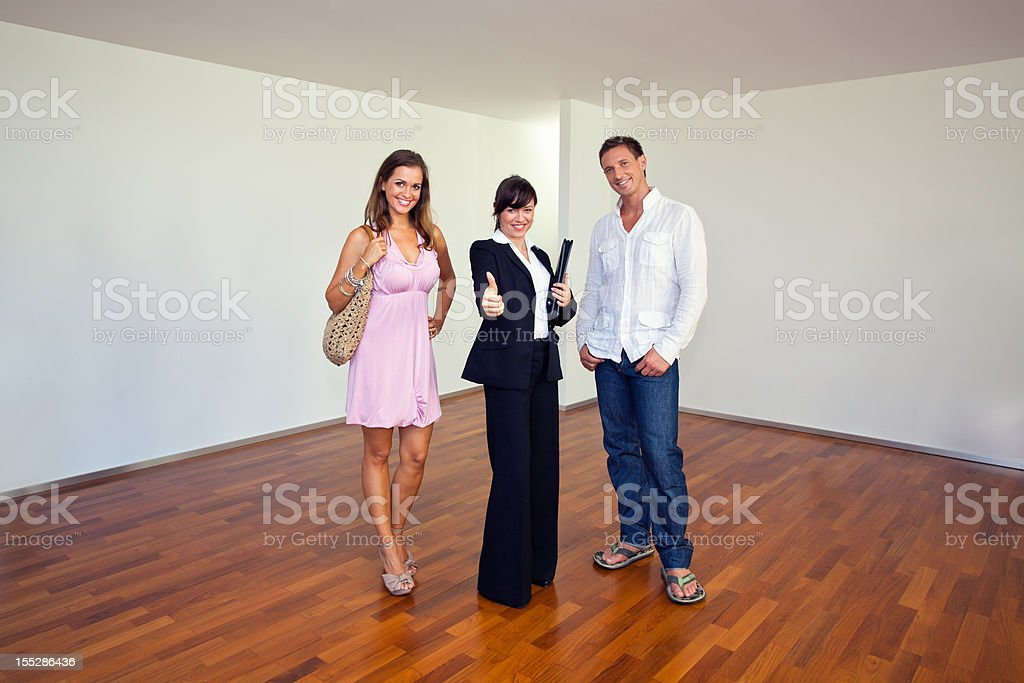 Real estate agent with customers looking at camera royalty-free stock photo