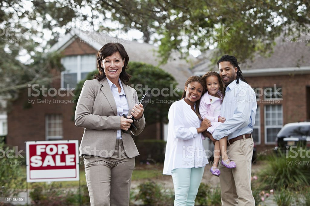 Real estate agent with family outside house stock photo