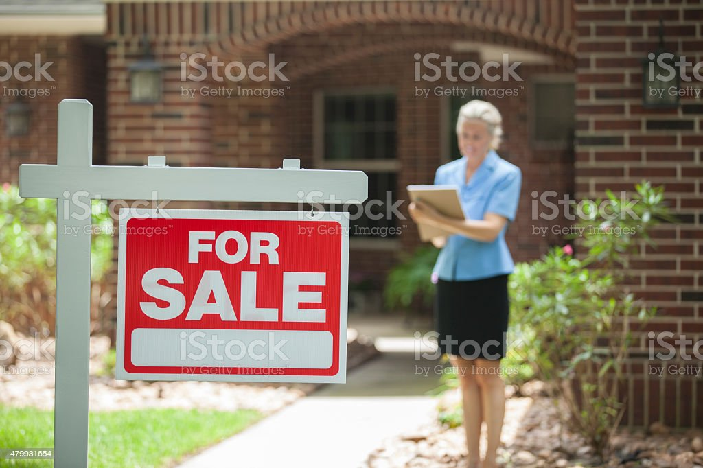 Real estate agent with home for sale, sign. House. stock photo