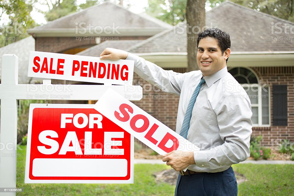 Real estate agent with home for sale, sold sign. stock photo