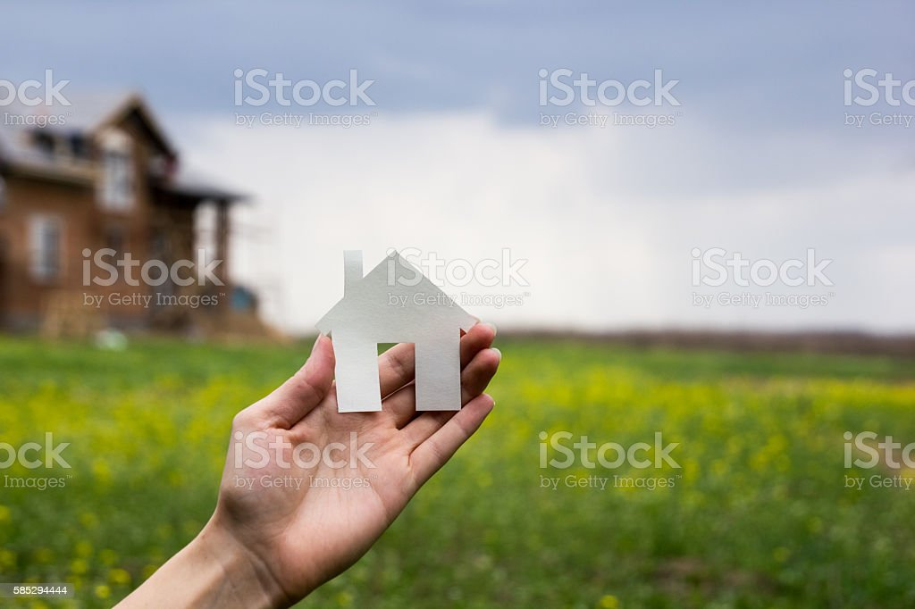 Real Estate Concept. Hand holding white paper house figure on stock photo