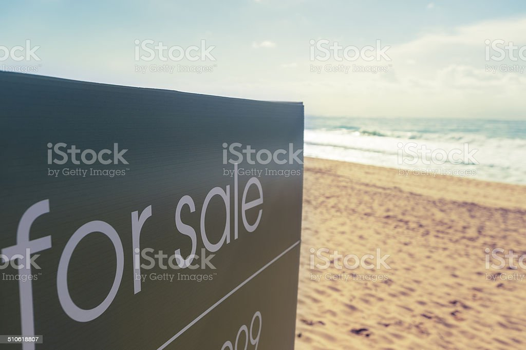 Real estate for sale sign on a beach stock photo