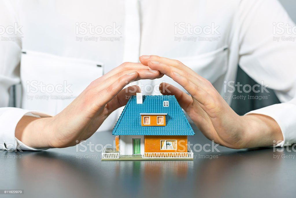 real estate insurance concept - human hands saving small house stock photo