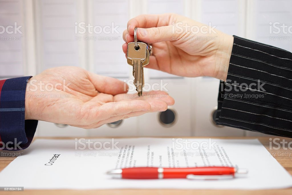 real estate seller is giving keys to buyer after signed stock photo