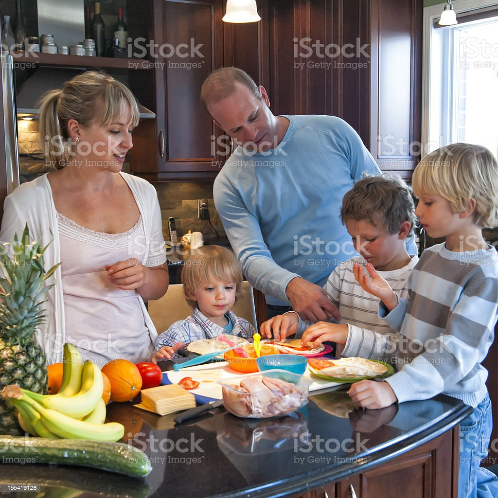Real family of five making healthy lunch in kitchen. stock photo