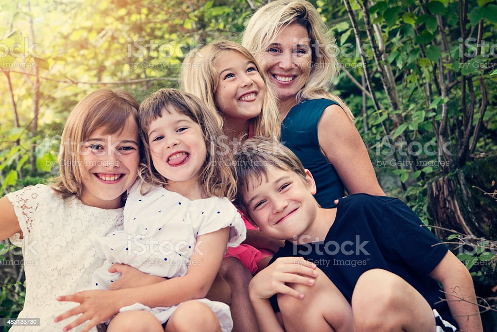 Real family of four kids posing with mother in summer. stock photo