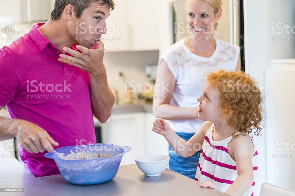 Real family of three making cake in the kitchen. royalty-free stock photo