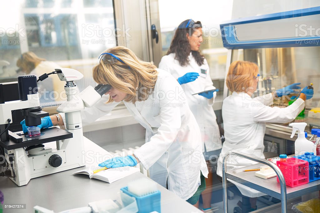 Real female scientists looking into a microscope stock photo