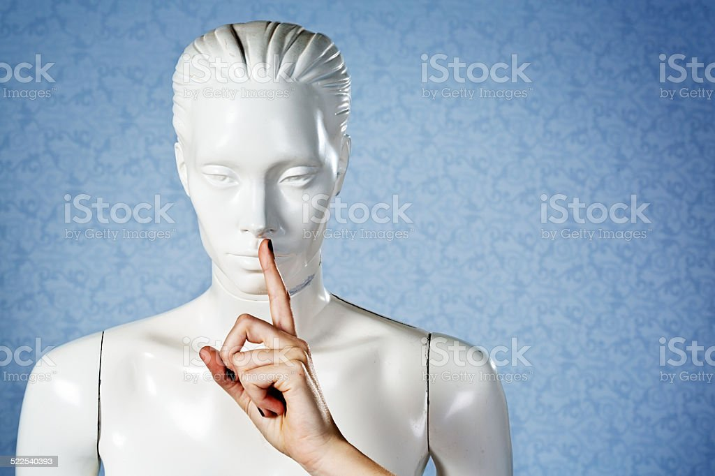 Real fingers make silencing gesture on window mannequin's mouth stock photo