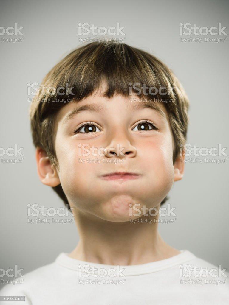 Real kid looking away with puffed cheeks stock photo