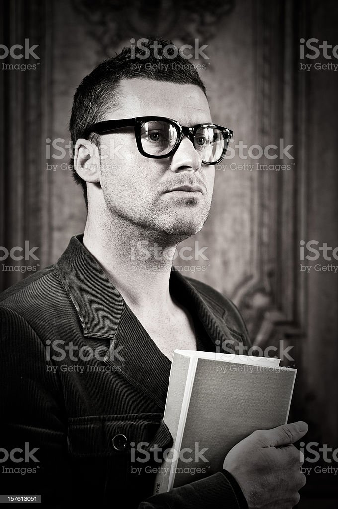 Real man with think rimmed glasses holding a book stock photo
